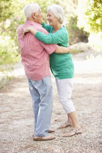 Senior Couple Dancing In Countryside Together
