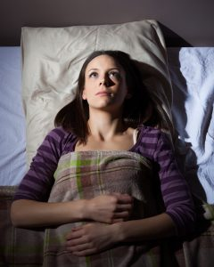 Young woman can not sleep. She is lying in her bed and thinking.