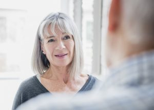 Woman in her 60s listening, with a pensive expression. The man is out of focus in the foreground.